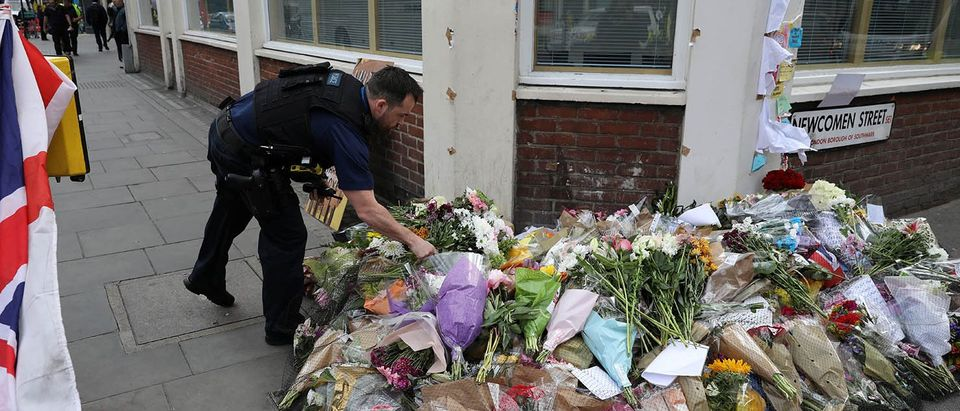 A police office touches floral tributes near the scene of the recent attack at London Bridge and Borough Market in central London