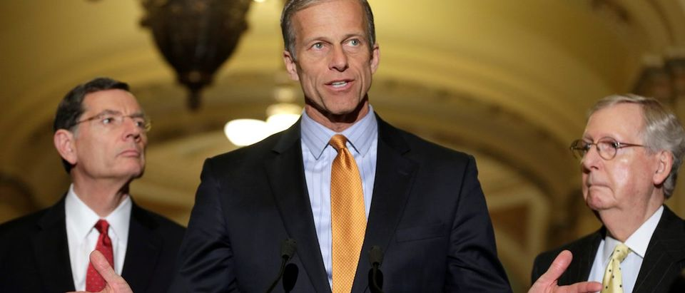 Senator John Thune (R-SD) speaks as Senate Majority Leader Mitch McConnell (R-KY) and Senator John Barrasso (L) listens during a media briefing on Capitol Hill in Washington