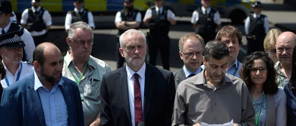 Jeremy Corbyn, the leader of Britain's opposition Labour Party stands next to Mohammed Kozbar as he reads a statement near to where a van was driven at muslims outside the mosque in North London