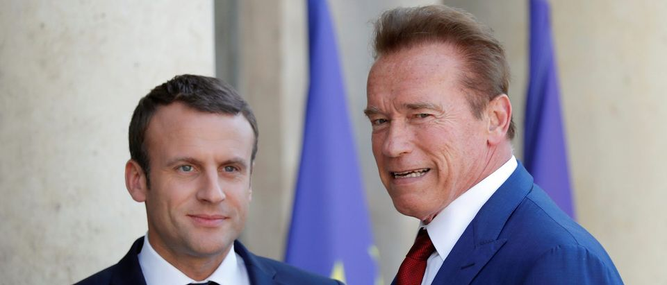 Former California Governor Arnold Schwarzenegger is greeted by French President Emmanuel Macron upon his arrival at the Elysee Palace in Paris