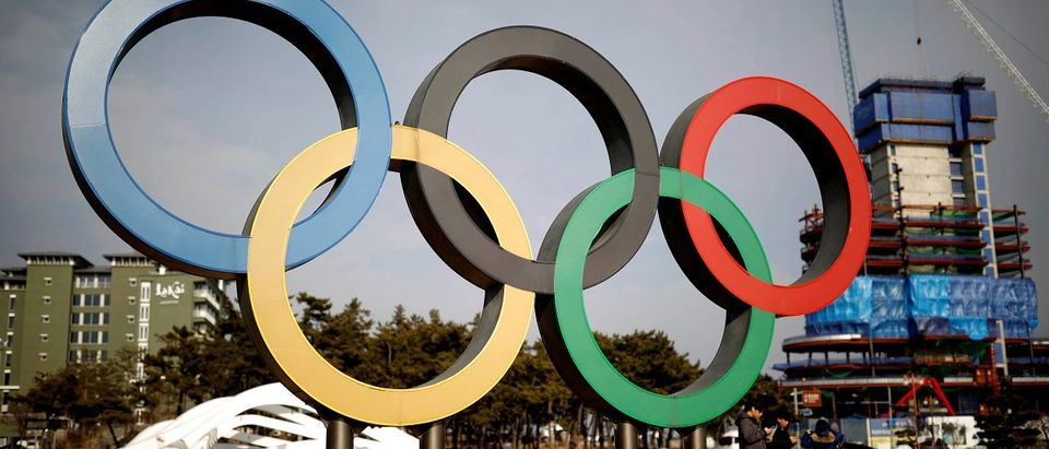 People walk past the Olympic rings in Gangneung