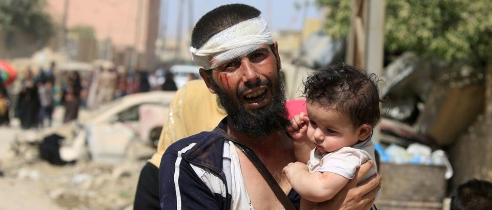 A wounded displaced Iraqi man who fled from clashes, carries his child in western Mosul