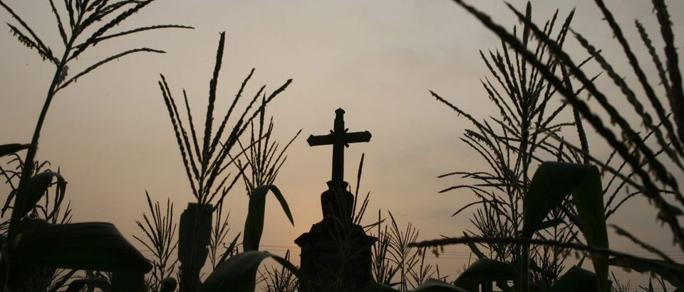 A cross stands at a corn field while sun set outside Hanoi