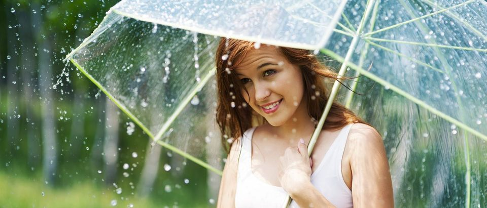 Beautiful woman with umbrella during the rain (Shutterstock/gpointstudio)