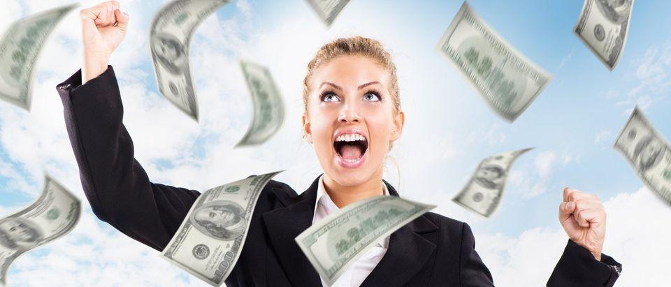 Happy Businesswoman under money rain. (Shutterstock/MilanMarkovic78)