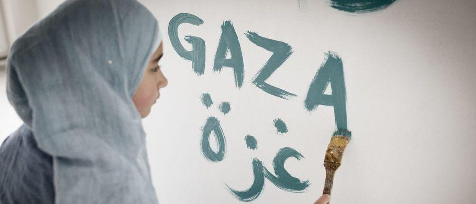 Shutterstock/ Arabic Muslim girl writing messages on board