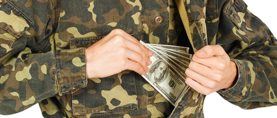 Army soldier pockets a cash bribe (Photo: Shutterstock/ GeniusKp)