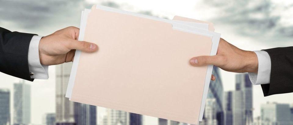 Handing over secret files. [Shutterstock - Billion Photos]
