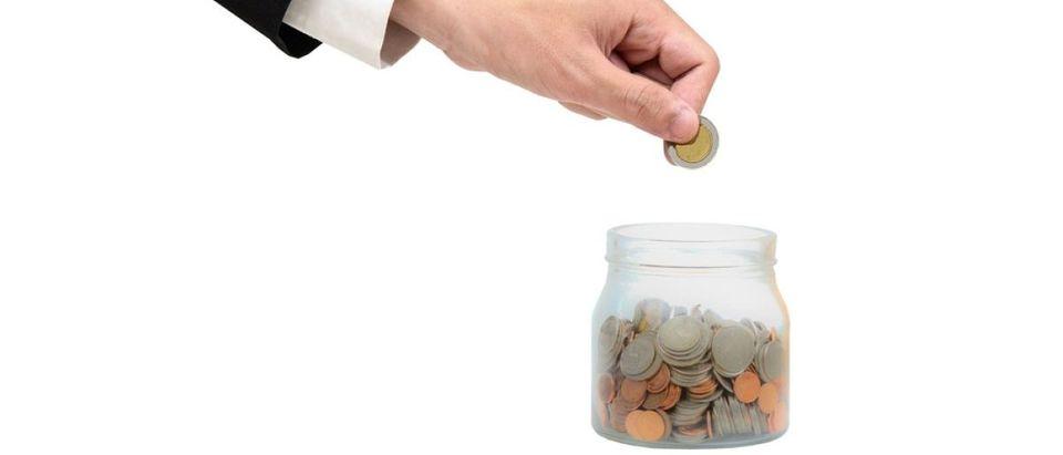 Man placing money in a tip jar. [Shutterstock - Prachaya Roekdeethaweesab]