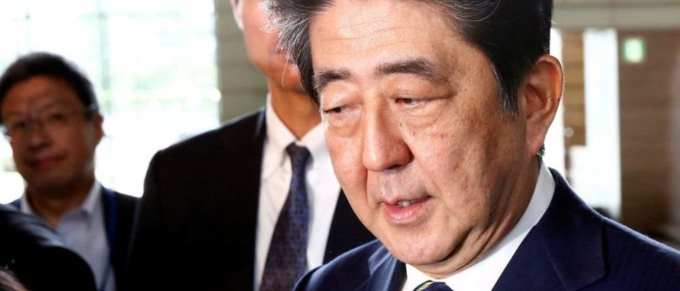 Japan's Prime Minister Shinzo Abe speaks to reporters as he arrives at his office in Tokyo