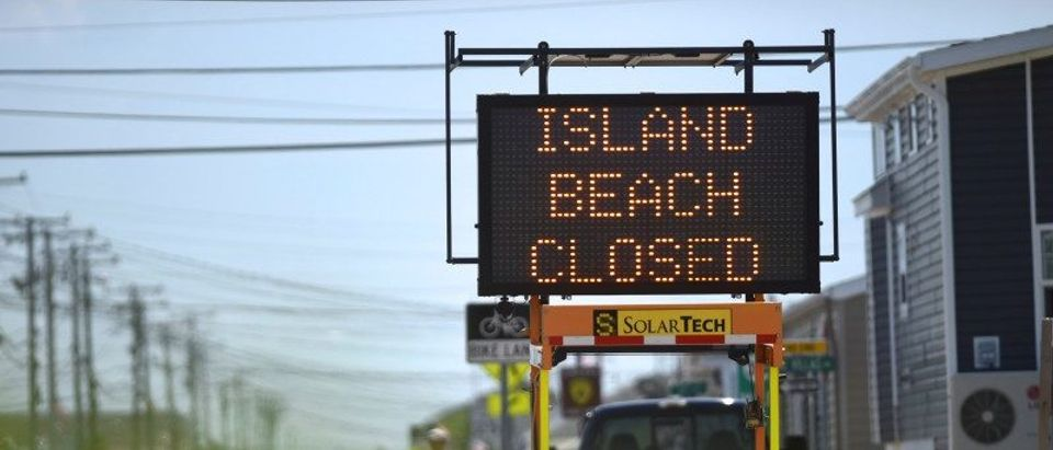 A construction sign alerts motorists that the Island Beach State Park is closed, due to a statewide facility shutdown, in Seaside Park, New Jersey