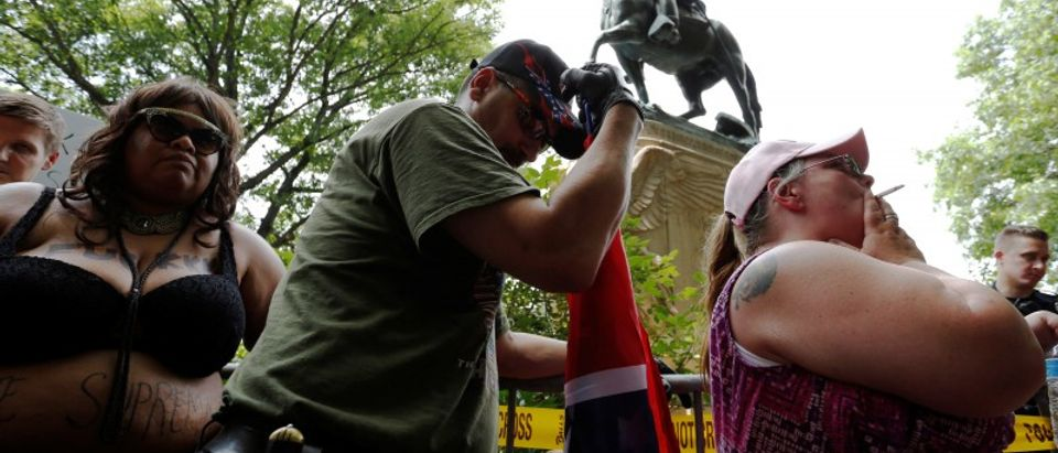 A woman who supports Confederate symbols and monuments relaxes with a cigarette after she and her husband exchanged words with a counter-protester as they wait for members of the Ku Klux Klan to rally in Charlottesville, Virginia