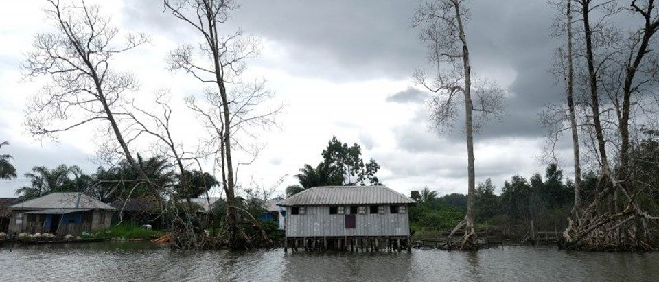 Small houses are seen by the bank of a river amidst polluted waterways in Gbaramatu kingdom, in Delta State