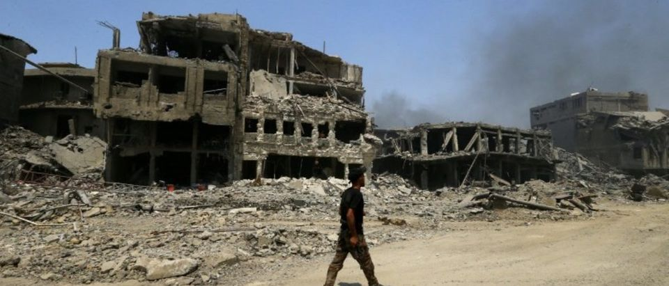 A member of Iraqi Counter Terrorism Service walks along destroyed buildings from clashes in the Old City of Mosul