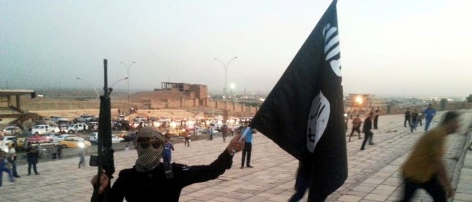 FILE PHOTO: ISIL fighter holds a flag and a weapon on a street in Mosul