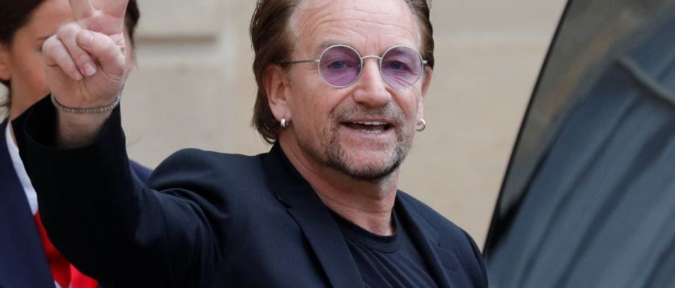 Singer Bono of Irish band U2 and co-founder of ONE organization waves as he leaves the Elysee Palace in Paris