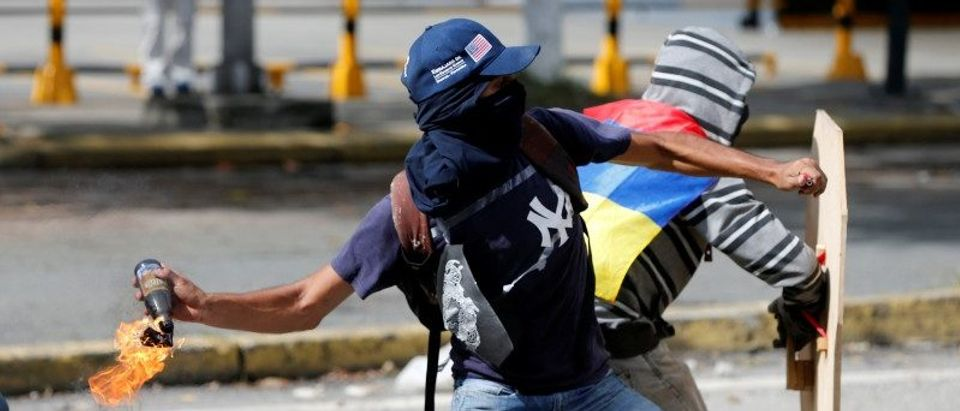 Demonstrators clash with riot security forces while rallying against Venezuela's President Maduro's government in Caracas