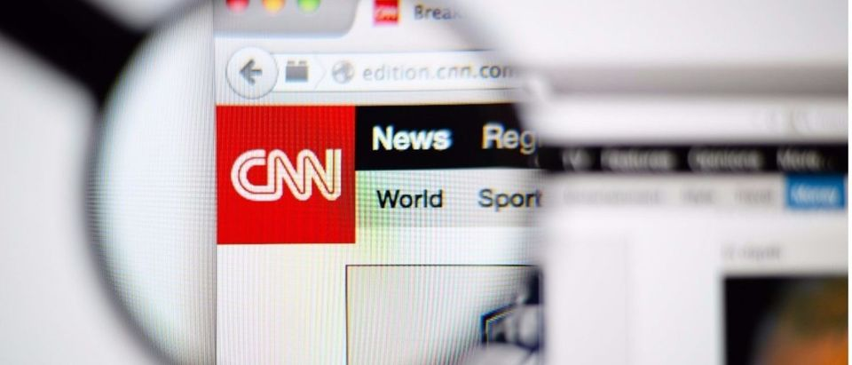 CNN homepage on a monitor screen through a magnifying glass. (Shutterstock/Gil C.)