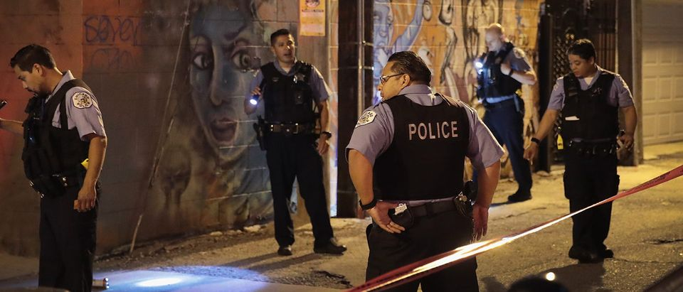 Police search for evidence after a man was shot in the Little Village neighborhood on July 2, 2017 in Chicago, Illinois. Five people were killed and about another 50 wounded in gunfire in the city over the holiday weekend. On June 1, a task force was formed by the Chicago police and state and federal law enforcement to combat gun violence in the city. (Photo by Scott Olson/Getty Images)