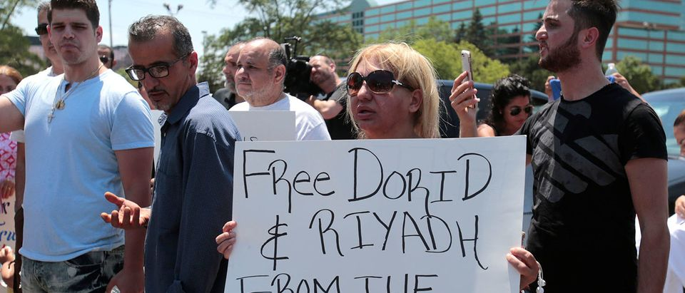Chaldean-American Nadia Al-Raviah holds a sign protesting against the seizure of her husband and brother Sunday by Immigration and Customs Enforcement agents, in Southfield