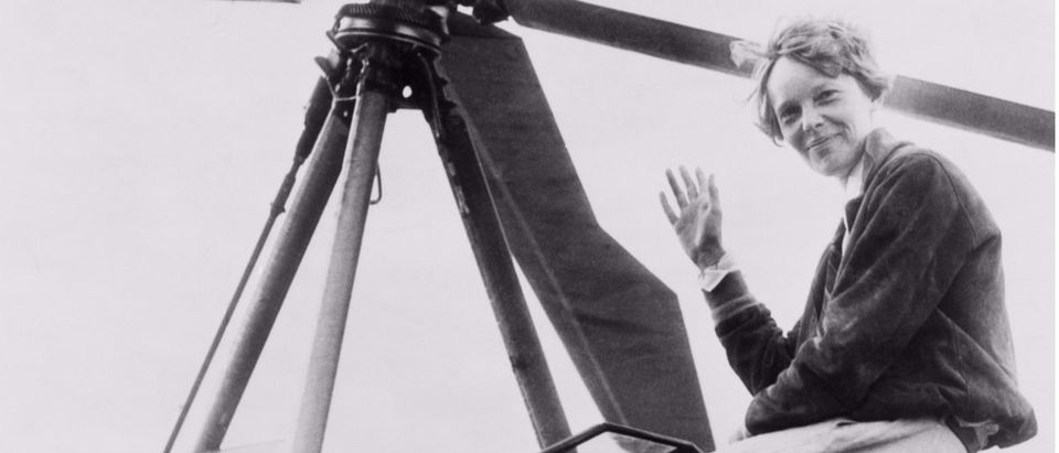 Amelia Earhart waving, seated outside cockpit on top of an Autogiro. Shutterstock/Everett Historical.