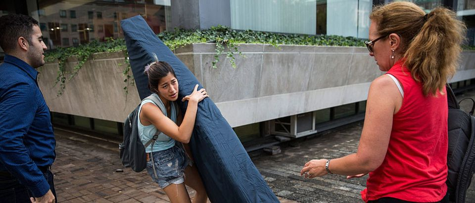 NEW YORK, NY - SEPTEMBER 05: Emma Sulkowicz (C), a senior visual arts student at Columbia University, is offered assistance by two strangers as she carries a mattress in protest of the university's lack of action after she reported being raped during her sophomore year on September 5, 2014 in New York City. Sulkowicz has said she is committed to carrying the mattress everywhere she goes until the university expels the rapist or he leaves. The protest is also doubling as her senior thesis project. (Photo by Andrew Burton/Getty Images)