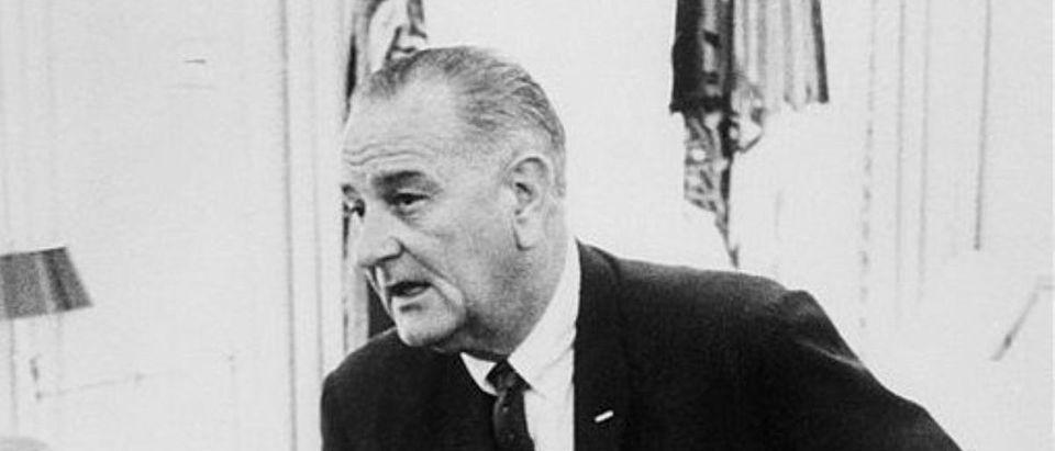 US President Lyndon B. Johnson (R) confers 08 Augu