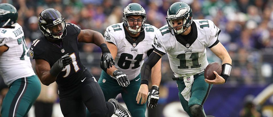 BALTIMORE, MD - DECEMBER 18: Quarterback Carson Wentz #11 of the Philadelphia Eagles carries the ball against linebacker Matt Judon #91 of the Baltimore Ravens in the first quarter at M&T Bank Stadium on December 18, 2016 in Baltimore, Maryland. (Photo by Patrick Smith/Getty Images)