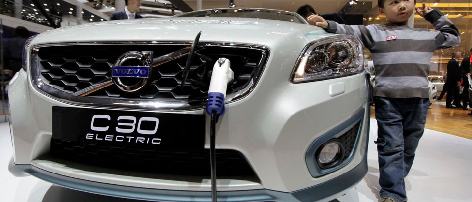 A boy poses for a photo next to a Volvo C30 Electric car at Auto China 2012 in Beijing April 23, 2012. Volvo plans to launch 10 new models in China by 2020, its chairman, Li Shufu, said on Monday on the sidelines of the Beijing Autoshow. REUTERS/Jason Lee