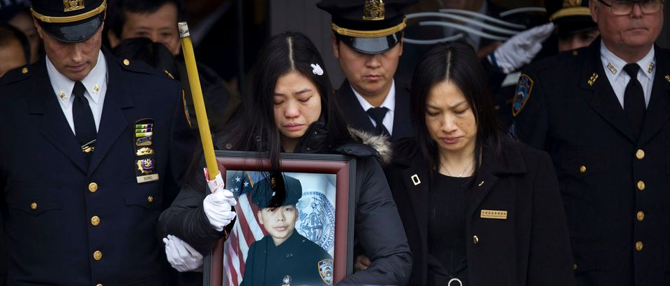 Widow Pei Xia Chen holds a photo of slain New York Police Department officer Wenjian Liu as his casket departs his funeral in the Brooklyn borough of New York