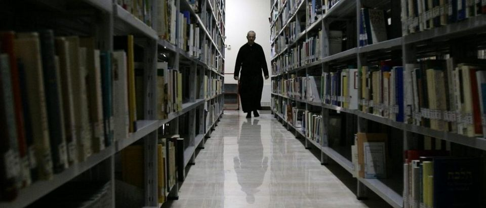 Professor at Rome's Regina Apolostolorum pontifical university walks though a libraby used in a new course on the occult. (Photo: REUTERS/Alessandro Bianchi)