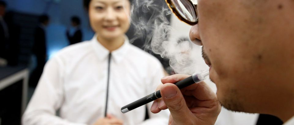A journalist tries out Japan Tobacco Inc's Ploom Tech smokeless vaping product at the Ploom Shop in Tokyo