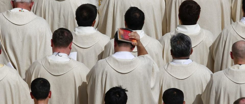 A priest covers his head with a book as Pope Francis celebrates a Jubilee mass in Saint Peter's Square at the Vatican