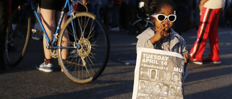 A girl holds a sign during a rally in Baltimore, Maryland May 2, 2015. Hundreds of people took to the streets of Baltimore on Saturday as anger over the death of a young black man turned to hopes for change following swift criminal charges against six police officers. REUTERS/Jim Bourg