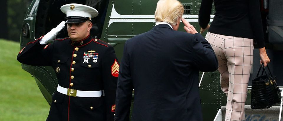 Trump returns a U.S. Marine's salute as he and the first lady board the Marine One helicopter to depart for travel to Poland in Washington