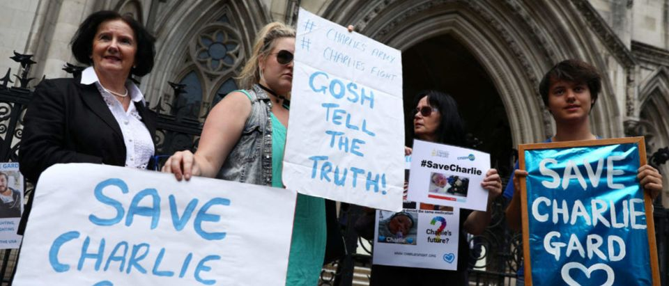 Campaigners hold up banners to show support for allowing Charlie Gard to travel to the United Stated to receive further treatment, outside the High Court in London