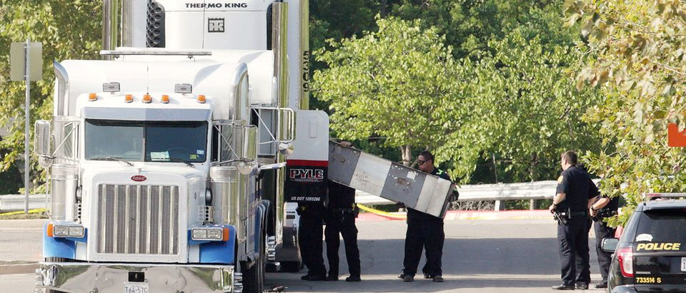 Police forensics officers work on a crime scene where eight people were found dead in San Antonio