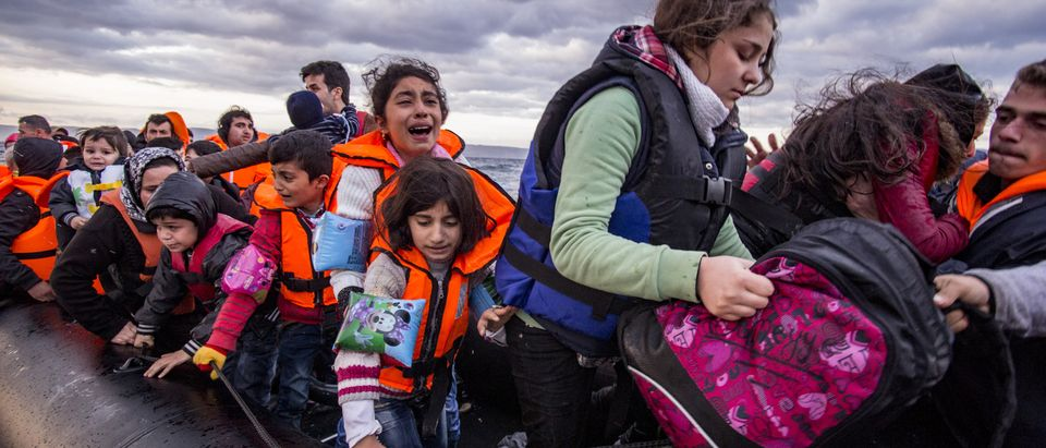 Shutterstock/ Lesvos island, Greece - 29 October 2015. Syrian migrants / refugees arrive from Turkey on boat through sea with cold water near Molyvos, Lesbos on an overload dinghy. Leaving Syria that has war.