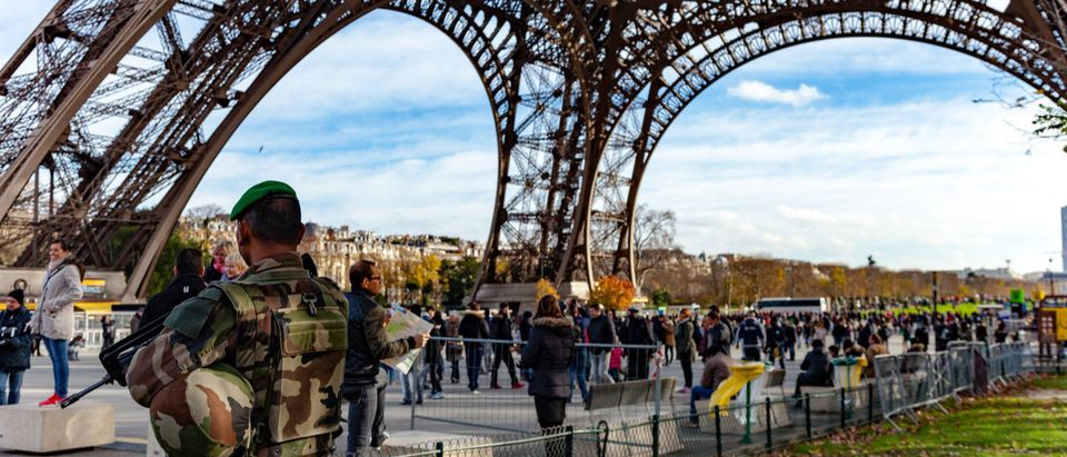 Shutterstock/ Paris, France - December 5, 2015: French soldier guarding the Eiffel Tower to prevent terrorism.