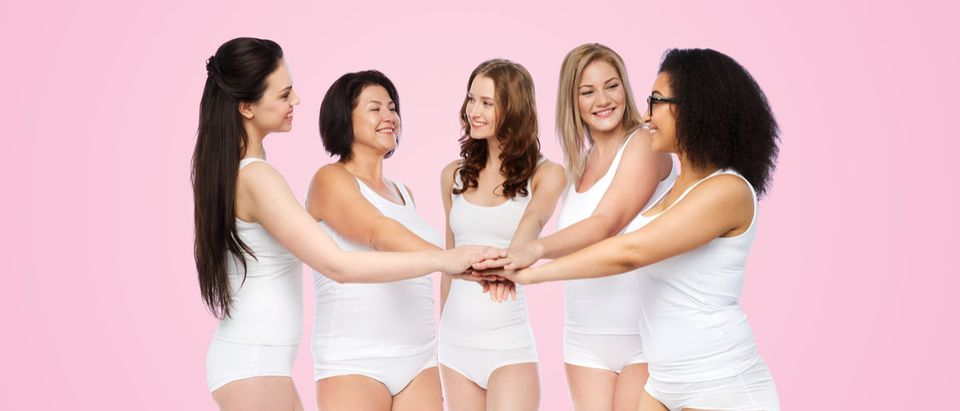 Shutterstock/ gesture, friendship, beauty, body positive and people concept - group of happy different women in white underwear holding hands together on top over pink background