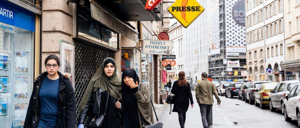 Shutterstock/ STRASBOURG, FRANCE - MAY 7, 2017: Three muslims girls walking on trottoir under Loto and press signage in French city of Strasbourg adultarabarabianarabicasianattractivebeardbusinesscityclothesclothingculturedresseastern cultureethnicethnicityfemalefrancefriendsfriendshipfull lengthgirlhandsomeheadscarfhijabislamislamicmiddlemiddle-east culturemuslimmuslim girlsoutdoorspedestrianspeoplepersonportraitreligionscarfstrasbourgstreettourismtraditionalwalkwhitewomenyoung muslimShow more