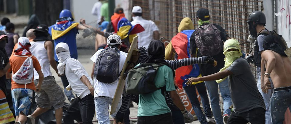 """Anti-government activists clash with the National Guard in Caracas on July 27, 2017 on the second day of a 48-hour general strike called by the opposition. Venezuela's opposition called for a nationwide protest on Friday in outright defiance of a new government ban on demonstrations ahead of a controversial weekend election. """"The regime declared we can't demonstrate... We will respond with the TAKING OF VENEZUELA tomorrow,"""" the opposition coalition, the Democratic Unity Roundtable, said Thursday on its Twitter account. (PHOTO: Getty Images/AFP/Juan BARRETO)"""