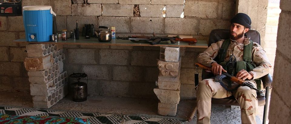 A Free Syrian Army fighter holds his weapon as he sits on a chair in rebel-held Al-Yadudah village, in Deraa Governorate