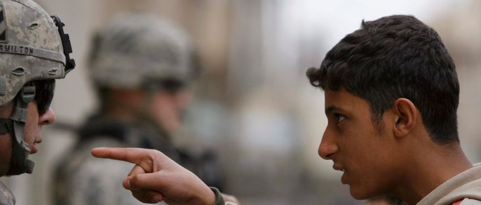 A resident gestures as he talks to a U.S. soldier from 2nd Brigade combat team, 82nd Airborne on patrol in Baghdad's Adhamiya district