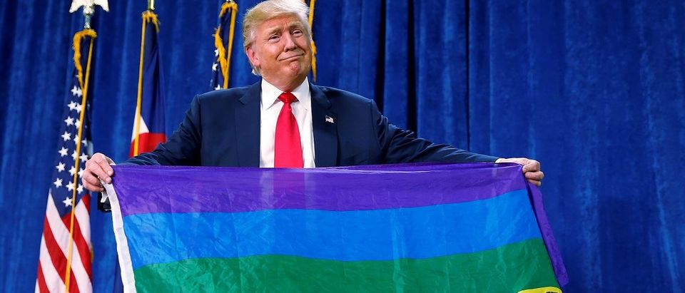 "Republican presidential nominee Donald Trump holds up a rainbow flag with ""LGBTs for TRUMP"" written on it at a campaign rally in Greeley"