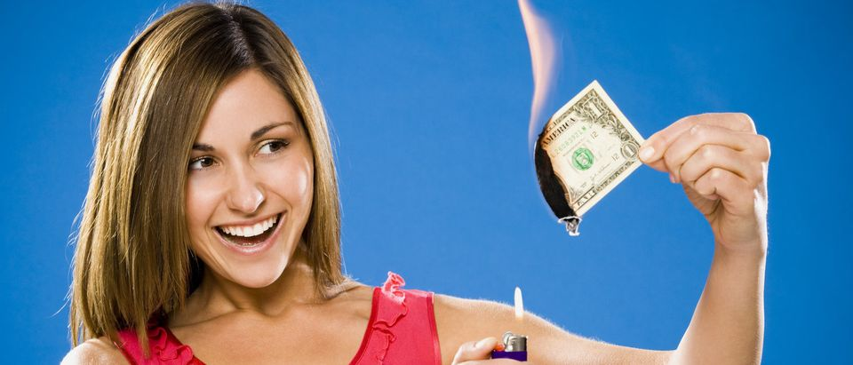 Woman setting American one dollar bill on fire (Shutterstock/Tiffany Bryant)