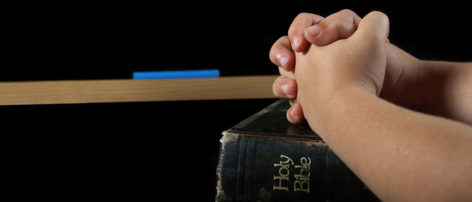 child's hands folded in prayer on a Holy bible with chalkboard (Maria Dryfhout/shutterstock_144339616)