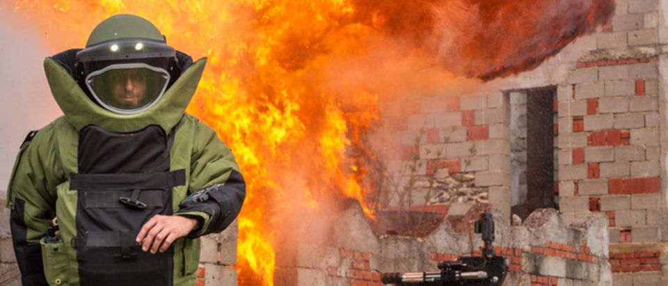 A bomb technician walks away from a burning house. Source: Milan Tomazin/Shutterstock