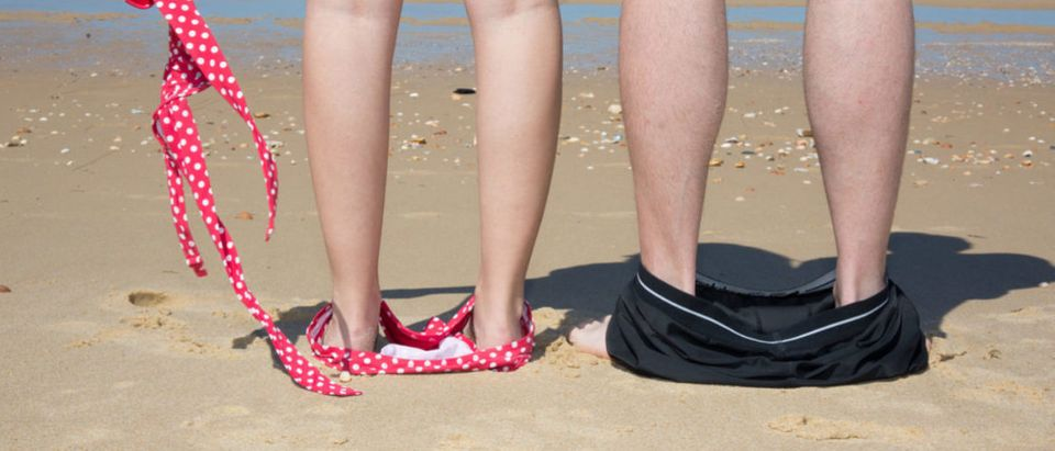 Naked couple standing on the beach with their swimwear on their feet (sylv1rob1/shutterstock_466208723)