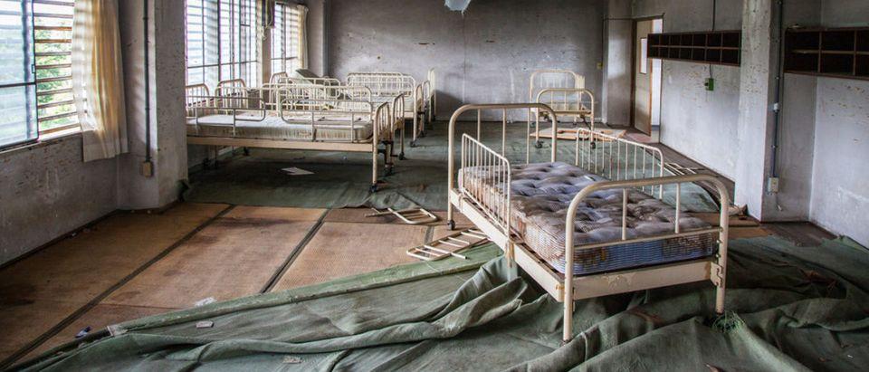 Empty beds in an abandoned building [Shutterstock - Benjamin Beech]
